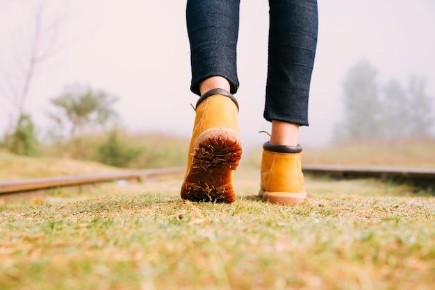Close-up girl viajeros botas caminando en el ferrocarril Foto gratis