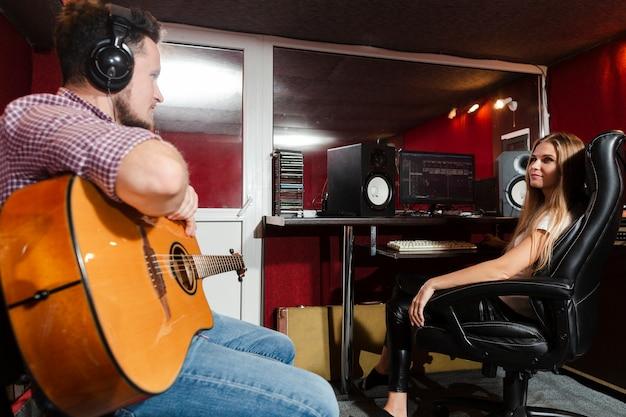 Close-up hombre tocando la guitarra en el estudio Foto gratis