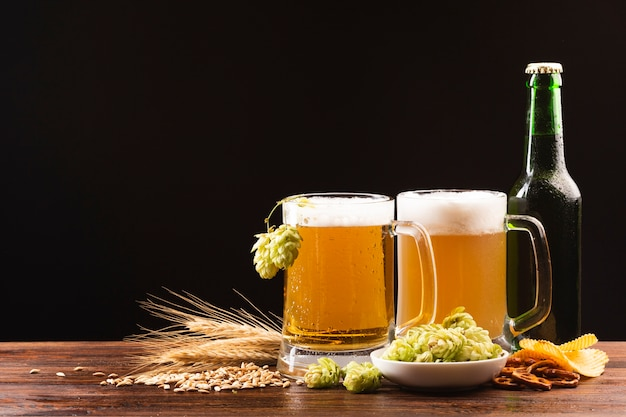 Close-up jarras de cerveza con ingredientes Foto gratis