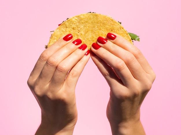 Close-up manos sosteniendo taco con fondo rosa Foto gratis