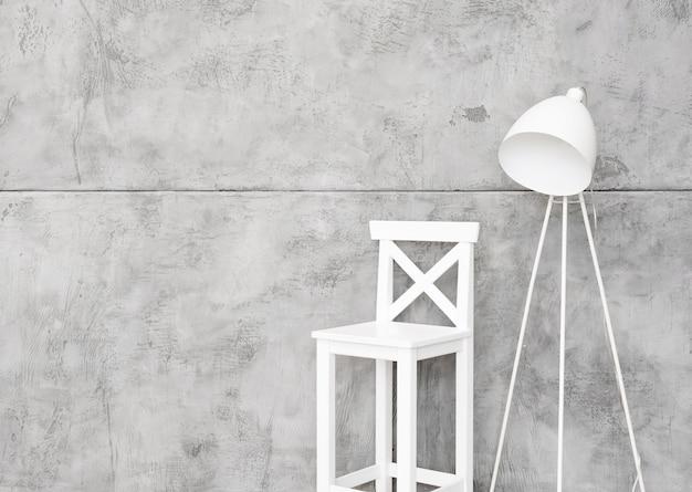 Close-up minimalista lámpara de pie blanca y taburete con paneles de hormigón Foto gratis