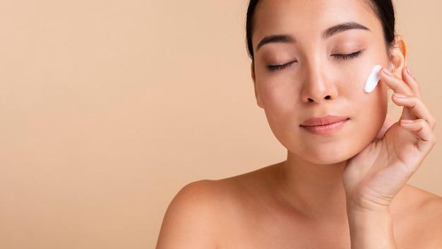 Close-up mujer asiática con crema para la cara Foto gratis