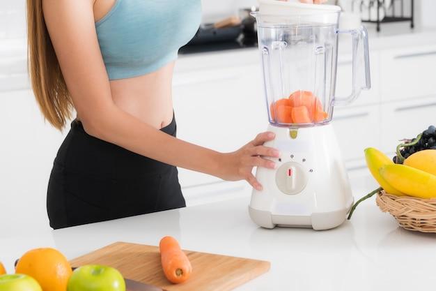Close-up mujer haciendo jugos de frutas y verduras con licuadora. Foto Premium