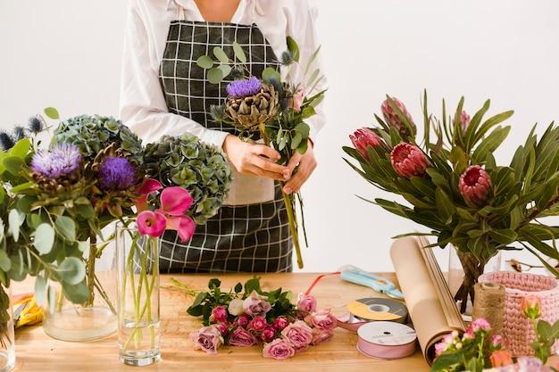 Close-up mujer que trabaja en la tienda de flores Foto gratis