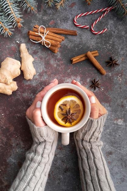 Close-up mujer sosteniendo la taza con té caliente Foto gratis