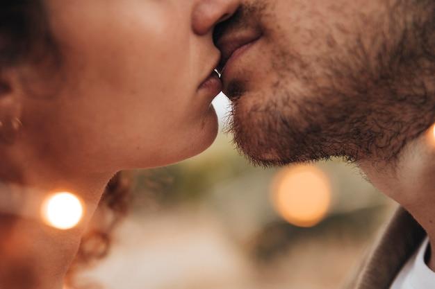 Close-up pareja besándose al aire libre Foto gratis