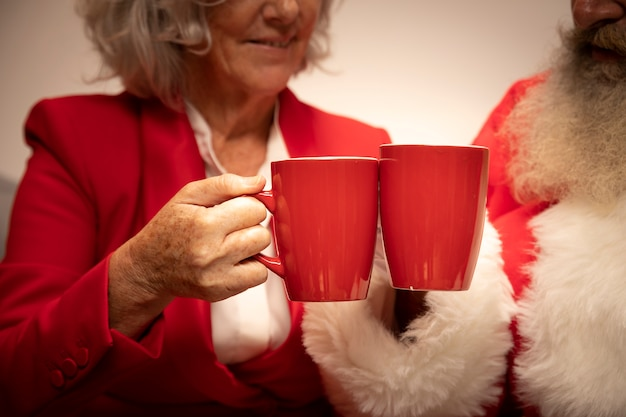Close-up pareja senior brindando con tazas Foto gratis