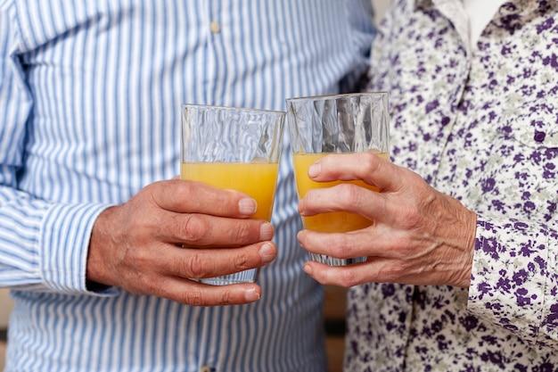 Close-up pareja sosteniendo copas con jugo Foto gratis