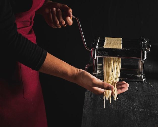 Close-up persona haciendo pasta con máquina Foto gratis