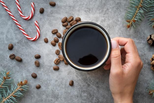 Close-up persona sosteniendo la taza de café con fondo de estuco Foto gratis