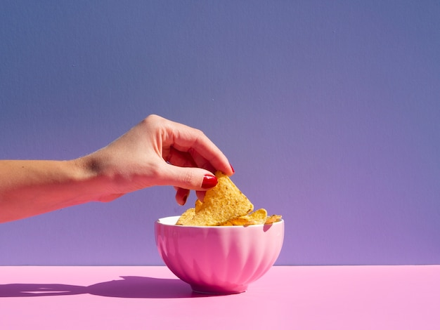 Close-up persona tomando tortilla de un tazón rosa Foto gratis