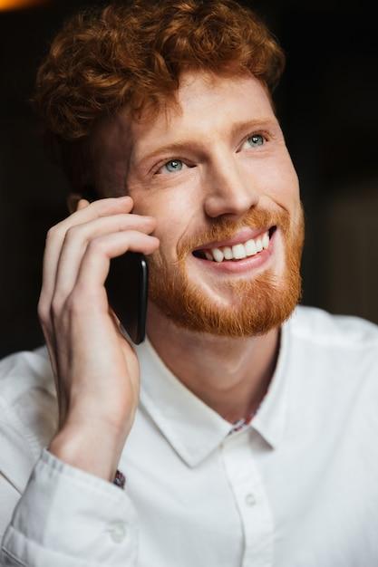 Close-up retrato de hombre guapo con barba pelirroja sonriente en camisa blanca tocando en el teléfono móvil Foto gratis