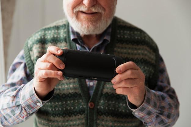 Close-up senior tocando música en el móvil Foto gratis