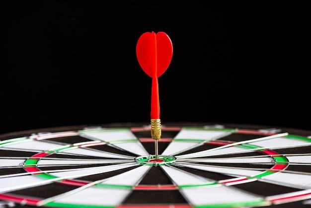 Close up shot dardos flechas rojas en el centro de destino sobre fondo negro Foto Premium