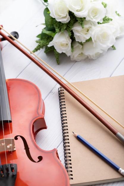 Close-up shot orquesta de violín instrumental y cuaderno sobre blanco madera seleccione foco profundidad de campo Foto Premium