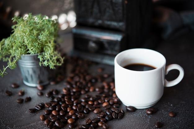Close-up taza de café con granos tostados Foto gratis