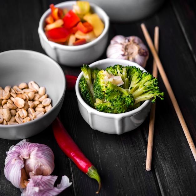 Close-up de verduras en tazas con ajo y palillos Foto gratis