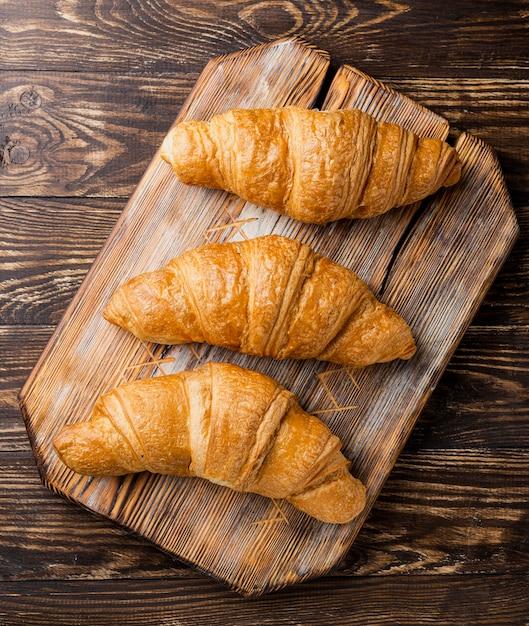 Close-up vista superior deliciosos croissants horneados en tablero de madera Foto gratis