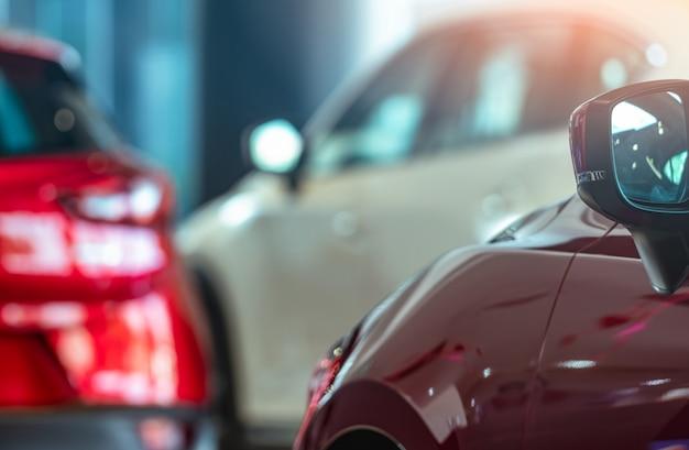 Closeup espejo lateral del coche rojo en suv borrosa estacionado en sala de exposición moderna. concesionario de coches. concepto de arrendamiento automático. stock de automóviles en showroom. Foto Premium