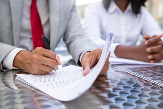 Closeup foto de empresario firmando documentos Foto gratis