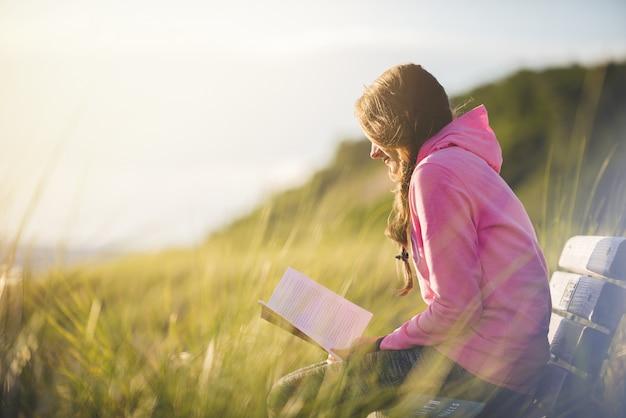 Closeup foto de una mujer sentada en el banco mientras lee la biblia en un campo de hierba Foto gratis