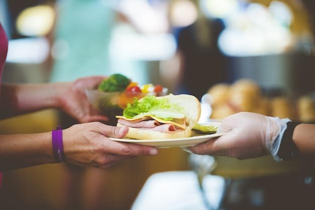 Closeup foto de una persona que sirve sandwich en un plato blanco Foto gratis