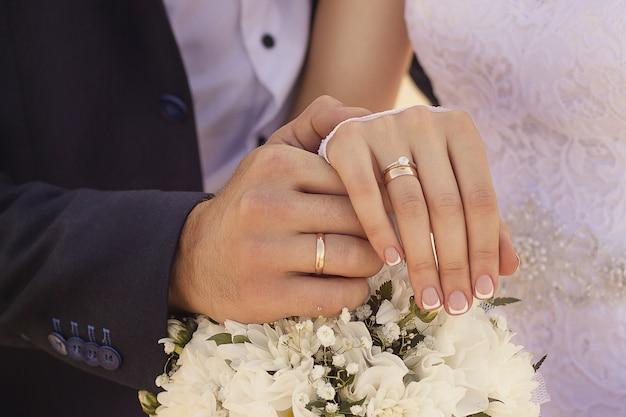 Closeup foto de recién casados cogidos de la mano y mostrando los anillos de boda Foto gratis