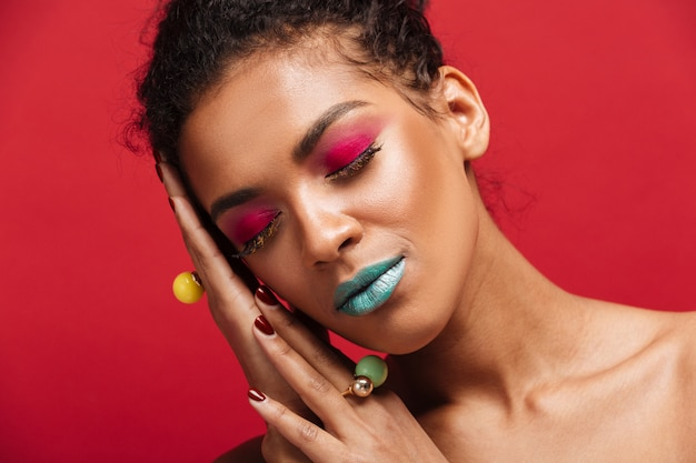 Closeup magnífica mujer afroamericana con maquillaje de moda cerrando los ojos y poniendo la cabeza en la palma, sobre la pared roja Foto gratis