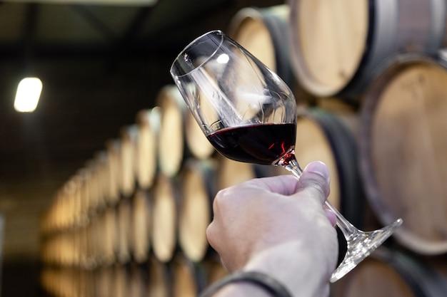 Closeup mano con vaso de vino tinto en el fondo de madera de barriles de roble apilados en filas rectas en orden, antigua bodega de la bodega. Foto Premium