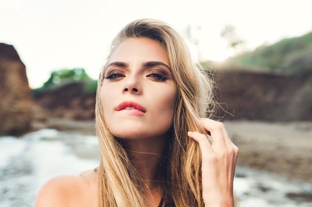 Closeup retrato de chica rubia sexy con cabello largo posando en la playa rocosa. se muerde los labios y mira a la cámara. Foto gratis
