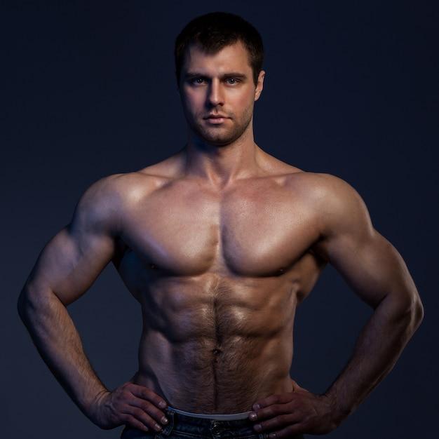 Closeup retrato de hombre musculoso en la oscuridad Foto gratis