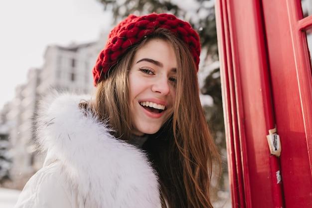 Closeup retrato increíble agradable joven con cabello largo morena, con sombrero rojo, expresando emociones positivas en la calle llena de nieve. tiempo de invierno frío, humor alegre. Foto gratis