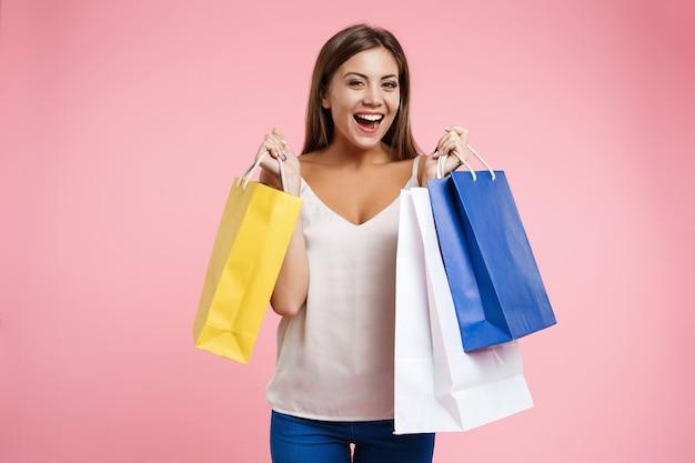 Closeup retrato de joven mujer feliz sosteniendo bolsas de compras Foto gratis