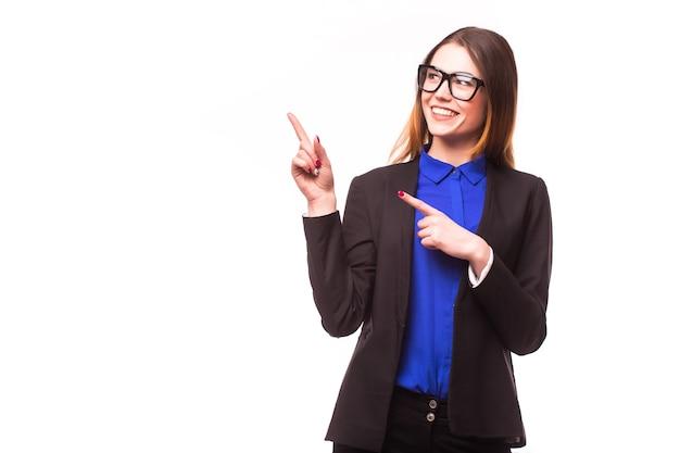 Closeup retrato de una mujer de negocios joven feliz apuntando a algo interesante contra la pared blanca Foto gratis