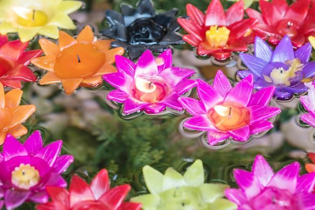 Closeup vela rosa en forma de flor en borrosa vela colorida flor flotando en el fondo con textura de agua Foto Premium
