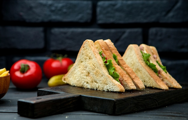 Club sandwich con pan crujiente sobre una plancha de madera Foto gratis