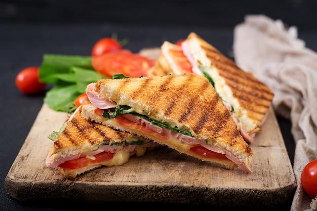 Club sandwich panini con jamón, tomate, queso y albahaca. Foto Premium