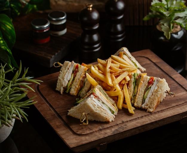 Club sándwiches para cuatro pax con papas fritas en un restaurante con hojas de romero Foto gratis