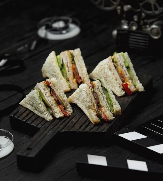 Club sándwiches en una tabla de madera negra Foto gratis