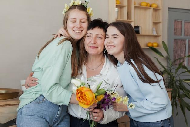 Club social femenino sosteniendo flores y abrazos Foto gratis
