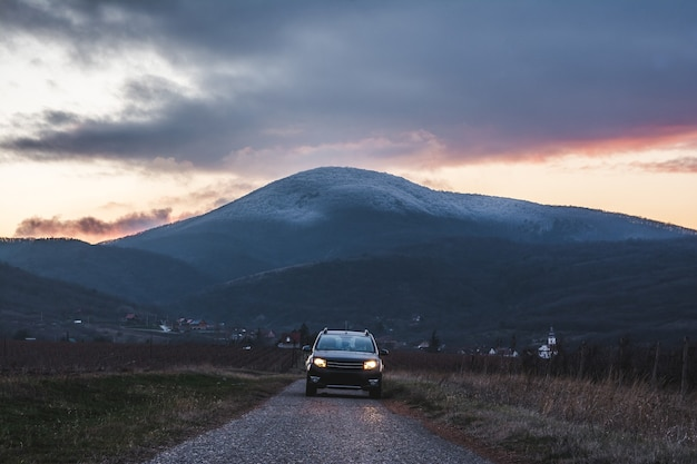 Coche en la carretera con una montaña durante la puesta de sol. Foto gratis
