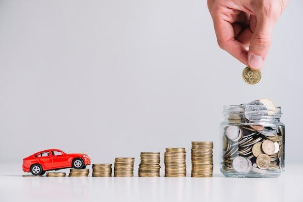 Coche conduciendo sobre el aumento de monedas apiladas cerca de la mano de la persona poniendo monedas en el tarro de cristal Foto Premium