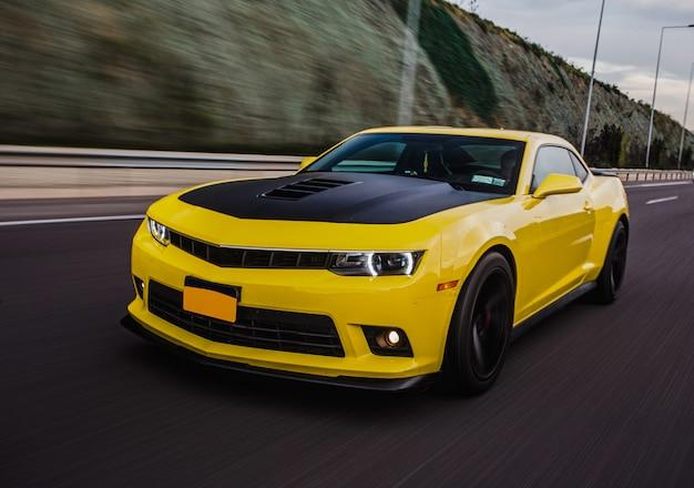 Coche deportivo amarillo con autotuning negro en la carretera. Foto gratis