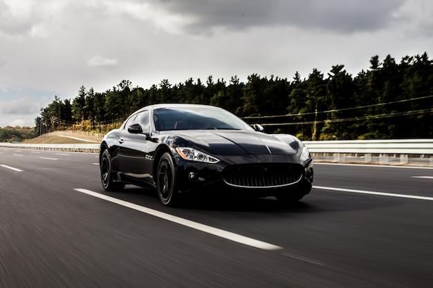Un coche deportivo coupe negro en la carretera. Foto gratis
