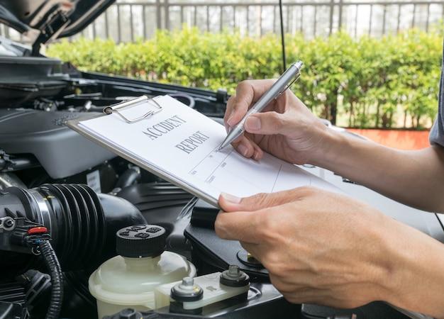 coche inspeccionando daños y llenando el formulario de informe de