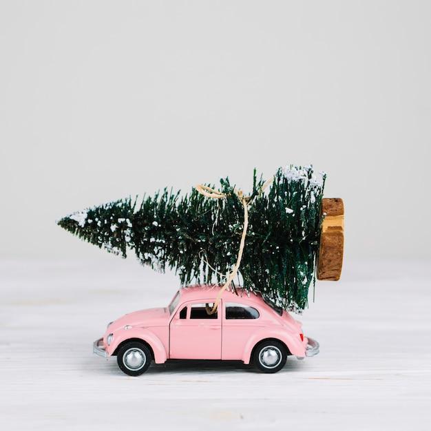 Coche miniatura con arbol de navidad. Foto gratis