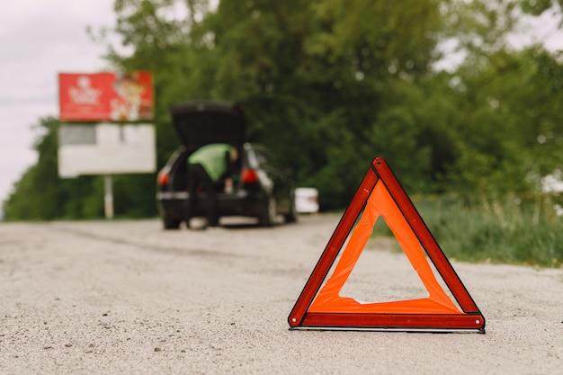 Coche con problemas y un triángulo rojo para advertir a otros usuarios de la carretera. Foto gratis