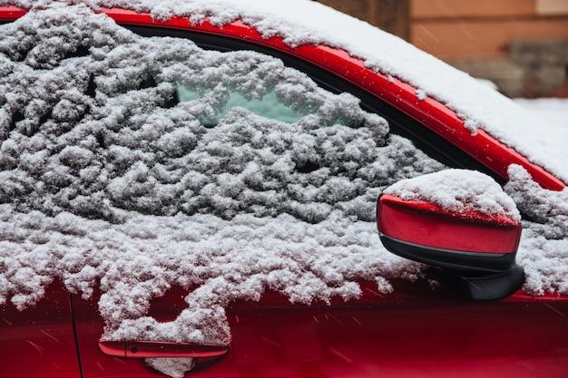 Coche rojo cubierto de nieve espesa. ventisca invernal y malas condiciones climáticas Foto Premium