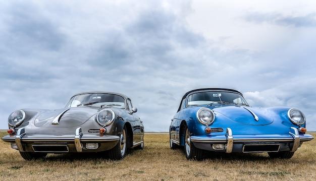 Coches grises y azules colocados uno al lado del otro bajo un cielo nublado Foto gratis