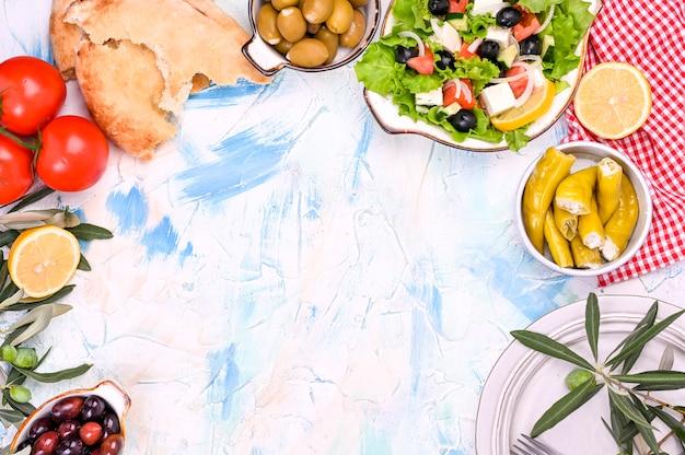Cocina tradicional griega. arroz envuelto en hojas de parra. dolma con limón, especias, varias aceitunas en escabeche y pimientos picantes. ramas frescas y comida casera. Foto Premium